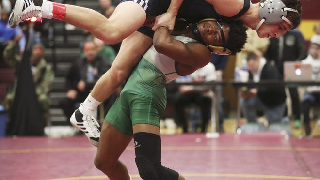 St. Vincent-St Mary's Dierre Clayton lifts Blair Academy's Ryan Miller in the 120-pound weight class during the quarterfinals of the Ironman in December.