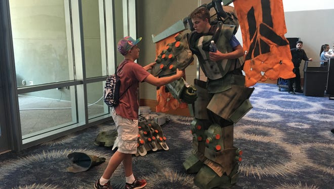 Seventeen-year-old Preston Woolsey of Scottsdale gets an assist out of his helmet and arms for a water break during Phoenix Comicon 2016. He made the costume, a bad guy from the video game Destiny.