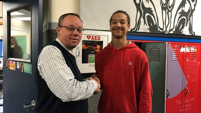 Calhoun Community HS Superintendent Tim Allard, left, shakes the hand of 2017 graduate Deshawn Amerson.