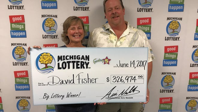 Brighton resident David Fisher and his sister Donna hold up a $326,974 check from Michigan Lottery in this photograph taken Wednesday, June 14, 2017 at the Michigan Lottery headquarters. Fisher won a Fantasy 5 Jackpot drawing Sunday June 11, 2017.