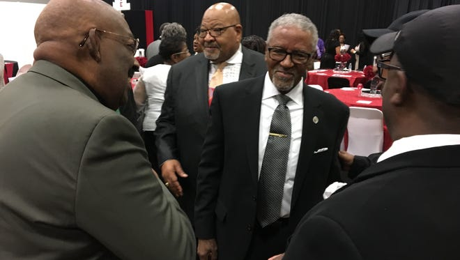 Bishop Carl H. Scott, center, is congratulated after being named a Ray Crenshaw neighborhood award honoree Saturday.