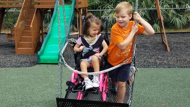 Aurora and Orion Gilmn play on the wheelchair swing at United Church of Sebatian's Special Needs Playground.