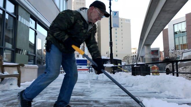 Walter Nemeth, 67, of  Southgate shovels snow for Queens Bar in downtown Detroit Thursday Dec. 14, 2017 after heavy snows hit the metro Detroit area.