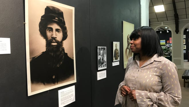 Sojourner Truth Institute of Battle Creek director Kimberly Holley looks at a photo of Kitchen Artis, a Calvin Township man who registered for the military in Battle Creek and served in an African American infantry unit of the Union Army from 1863-65.