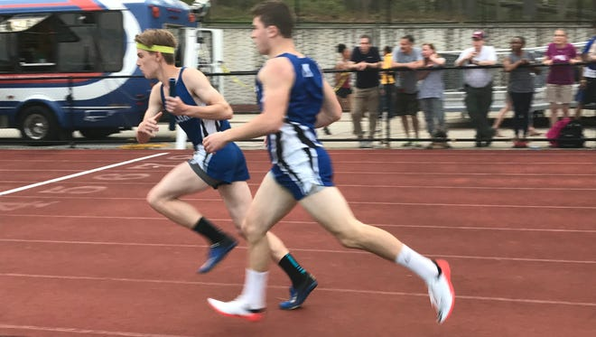Millburn's Griffin Titan (left) is handed the baton in a relay for the Millers.