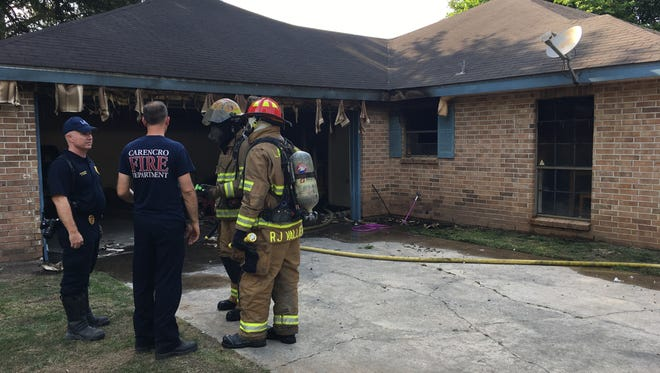 Firefighters stand outside the fire-damaged house in the 100 block of Potomac Drive in Carencro after extinguishing the fire Wednesday afternoon.