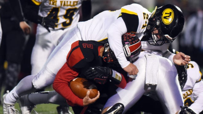 Chase Kendrick tackles Dezmin Lyburtus during Tri-Valley's 36-30 overtime win against Bellefontaine on Friday in a Division III regional semifinal game at Westerville Central. Kendrick is one of the Scotties tasked with fending off a potent Columbus Hartley running game in the regional finals.