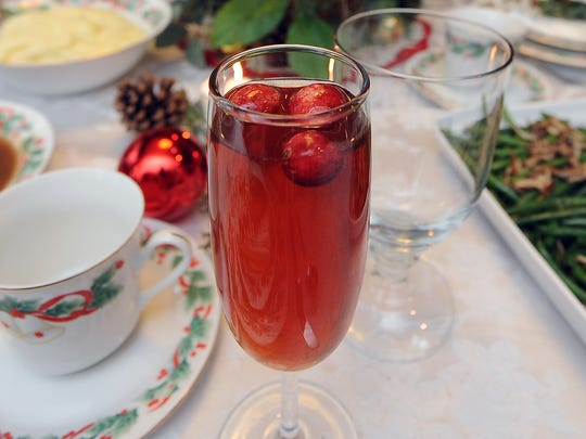 A sparkling cranberry tea cocktail gets an added touch of cranberries floating in the drink.