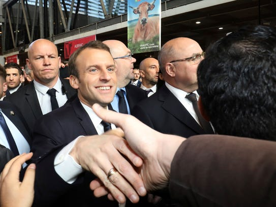 French President Emmanuel Macron shakes hands as he