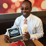 Necessary Luxury: Delano Wilson poses with his five favorite things. His cross Calligraphy and fountain pens. A Carolina Herrera journal. His Maxwell Leadership Bible. An iPad and large sweet tea from McDonalds.