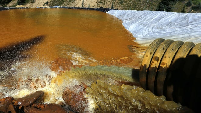 In this Aug. 14, 2015 photo, water flows through a series of retention ponds built to contain and filter out heavy metals and chemicals from the Gold King mine chemical accident, in the spillway about 1/4 mile downstream from the mine, outside Silverton, Colo. Researchers who studied a river in Colorado after a massive mine spill say runoff from fall storms kicked up the levels of some contaminants in the water but not others.