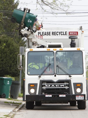 Sharon Johnston of Rumpke Recycling dumps bins along Park Avenue in Walnut Hills in 2012. Material in the back of a residential recycling truck caught fire June 16 on Weller Road in Montgomery, prompting Montgomery Fire Department to respond and for Rumpke to issue an important reminder to customers.