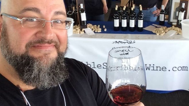 Dean Wilson, owner of Scribble Scribble Wines, holds a glass of Lucille, a 2014 Zinfandel named after his youngest daughter.