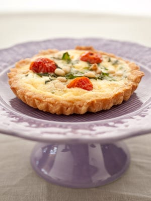 A prebaked crust holds this individual quiche with roasted cherry tomatoes, arugula, goat cheese and pine nuts by Linda Hopkins of Les Petites Gourmettes Cooking School in Scottsdale.