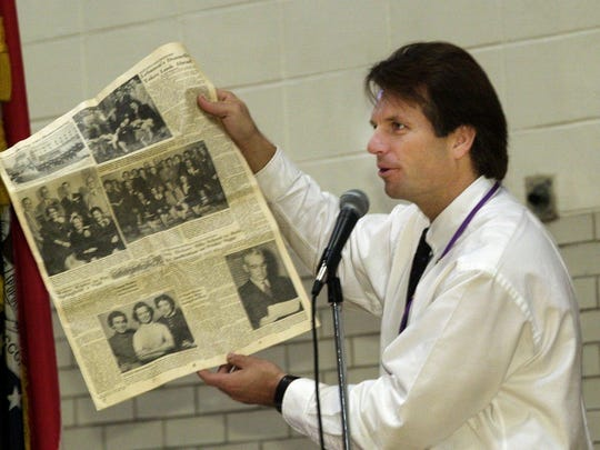 During a 50-year celebration of Hickory Hills school in 2002, principal Kelly Allison shows the audience items that were kept in a time capsule.