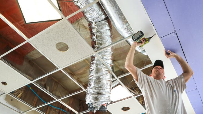 Robert Dupree instals drywall during renovations at Arby's on North Main Street in Anderson.
