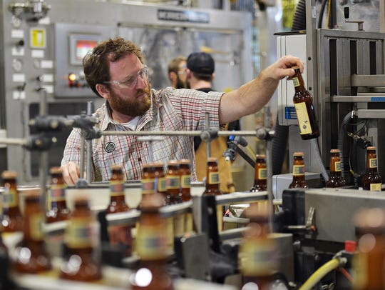 John Baise, packaging manager, checks labels on Odell's