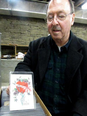 Rubin's Newsstand owner Geoff Rubin shows off one of the vintage greeting cards his grandfather sold at the store in the early 1900s.