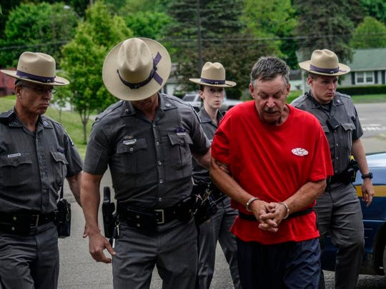New York State Police lead Almond Upton into Chenango Town Court in May 2014 for his arraignment on a first-degree murder charge in the death of Trooper Christopher G. Skinner.