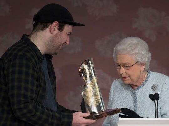 Queen Elizabeth presents fashion designer Richard Quinn