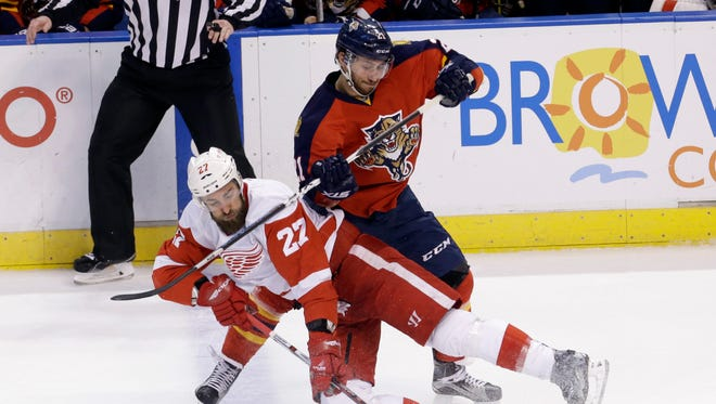 Florida Panthers center Vincent Trocheck (Saginaw Spirit, Plymouth Whalers) checks Detroit Red Wings defenseman Kyle Quincey, left, during the first period Feb. 4, 2016, Sunrise, Fla.