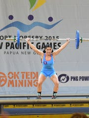 In this file photo, Guam weightlifter Kimberly Taguacta rises up to complete a 62-kilogram snatch at the Sir John Guise Indoor Gymnasium to secure Guam's first individual medal at the 2015 Pacific Games at the Port Moresby, Papua New Guinea.