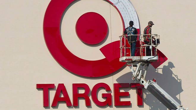 Workers install an outdoor sign at the new Target store at the Mic Mac Mall in Dartmouth, Nova Scotia, on July 20, 2013.