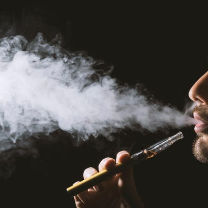 Young man holding and vaping an electronic cigarette,