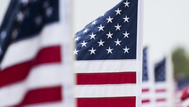 American Flags wave at a ceremony to recognize Lubbock area service members who have died from COVID-19 on Saturday, July 4, 2020, at the Monument of Courage in Lubbock, Texas.
