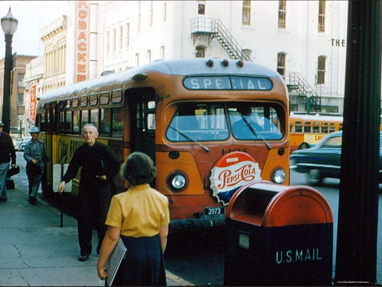 The bus drops off a passenger near the Reed's building in the 1950s.