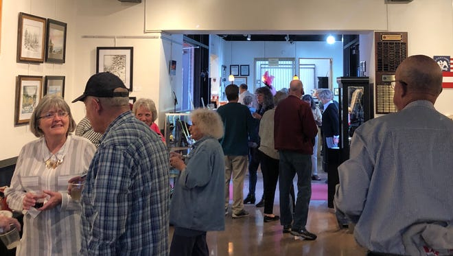 Spectators browse the gallery during an open house at the Mesquite Fine Arts Center on March 22, 2018.