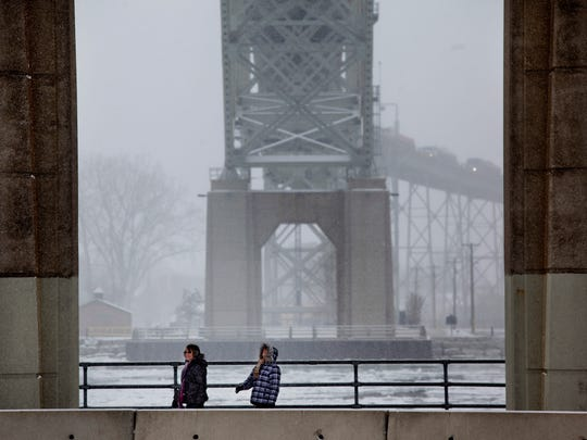 Two people walk under the westbound span of the Blue Water Bridge Tuesday afternoon in Port Huron. The span will be closed for resurfacing beginning in April and will reopen by July 1. All traffic will be diverted to the eastbound span.