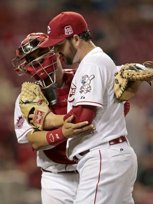Reds catcher Brayan Pena  and relief pitcher Donovan Hand hug after getting out of a jam in the top of the 12th inning.