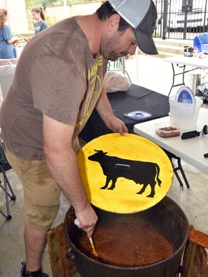 Derek Trahan stirs a pot of chili at St. Richard Catholic School during a chili cook-off at the Jackson school Sunday.