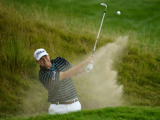 Bill Haas hits out of a bunker on the 18th hole during the first round of the PGA Championship golf tournament Thursday, Aug. 13, 2015, at Whistling Straits in Haven, Wis.