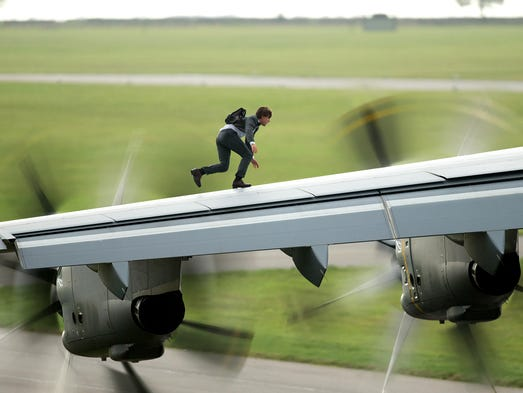 Tom Cruise runs along the wing of an A400 airplane