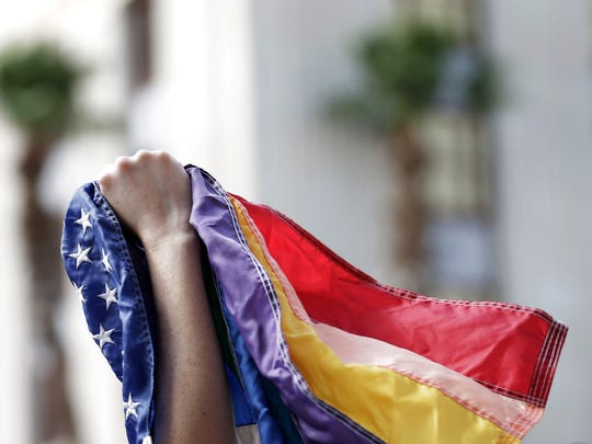 El Pasoan David Mendoza holds a multi-colored flag in his fist during a press conference in front of the El Paso County Courhouse as city and county leaders gathered to show their support and solidarity to the victims of the mass killing in Orlando.