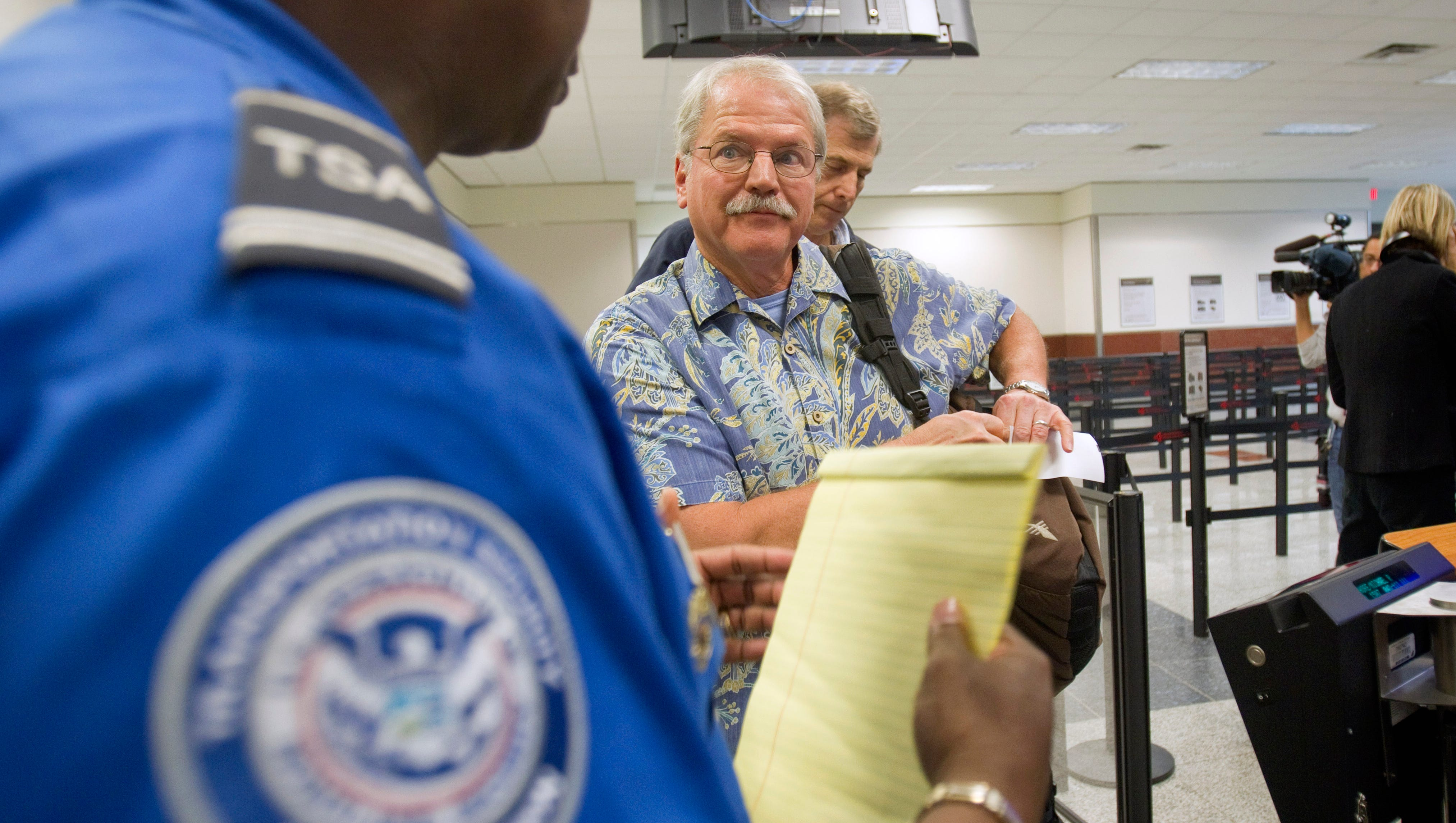 Don Heim of Alpharetta, Ga., is briefed by Transportation Security Administration trainer Byron Gibson before going through security at Hartsfield-Jackson International Airport in Atlanta in 2011.  Airport workers are on the front lines in screening passengers in light of the Ebola outbreak.