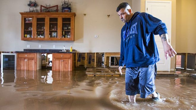 Nick Kriaris makes his way through his living room near 19th Ave. and Dobbins Road Monday morning after record-setting rainfall caused massive flooding throughout the Valley on Sept 8. 2014.
