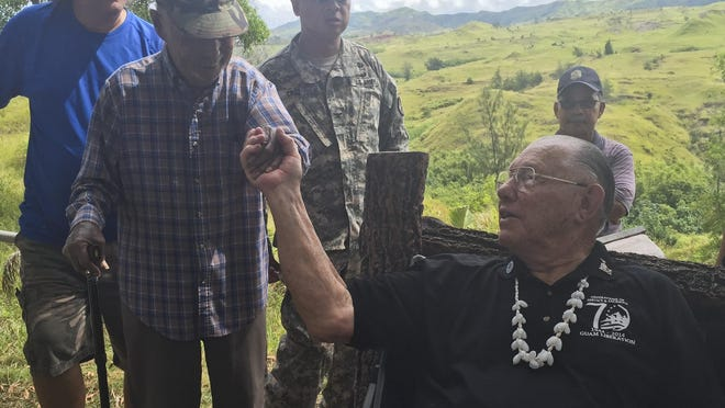 """""""Uncle"""" Buck Cruz, 3rd Marines, second from left, shakes hands with Gene Bell, 3rd Marines and Guam liberator, during a 2015 memorial for victims and survivors of the 1944 Faha Massacre. Families are asked to contact the Merizo Mayor's Office regarding the potluck assignment for this year's Tinta and Faha site visitation."""