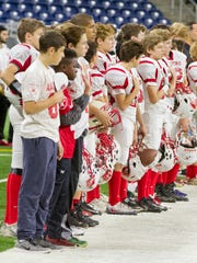 St. Regis players line up for the national anthem prior to the recent CYO championship game against Holy Family at Ford Field.