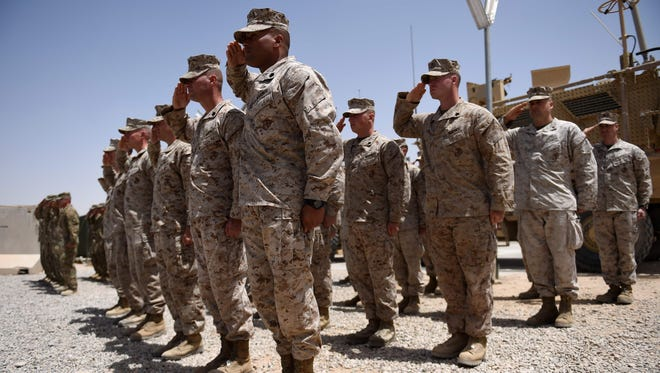"""U.S. Marines salute during a handover ceremony at Leatherneck Camp in Lashkar Gah in the Afghan province of Helmand on April 29.  US Marines returned to Afghanistan's volatile Helmand April 29, where American troops faced heated fighting until NATO's combat mission ended in 2014, as embattled Afghan security forces struggle to beat back the resurgent Taliban. The deployment of some 300 Marines to the poppy-growing southern province came one day after the militants announced the launch of their """"spring offensive"""", and as the Trump administration seeks to craft a new strategy in Afghanistan. / AFP PHOTO / WAKIL KOHSARWAKIL KOHSAR/AFP/Getty Images ORIG FILE ID: AFP_NZ1SO"""