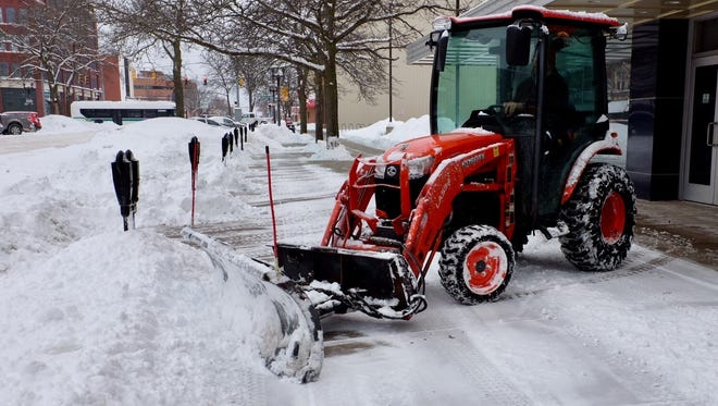 Snow removal crews clear sidewalks and around parking meters in downtown Lansing Sunday, Feb. 11, 2018.