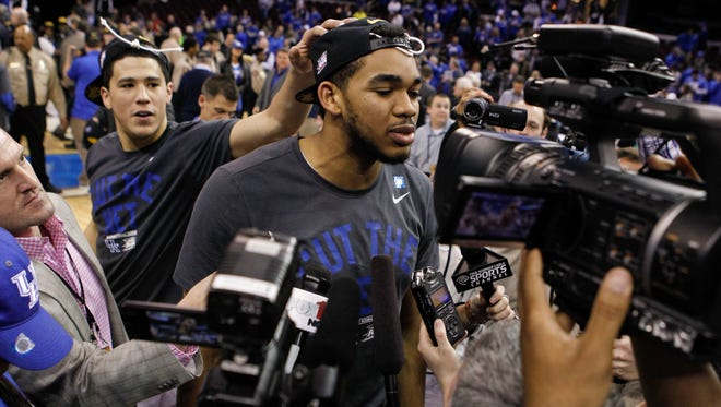 Kentucky's Karl-Anthony Towns talks with the media as teammate Devin Booker pats him on the head after the Wildcats defeated Notre Dame in the Elite Eight game Saturday at Quicken Loans Arena in Cleveland.  The Wildcats go on to the Final Four in Indianapolis. Towns lead the Cats with 25 points and was the main reason the Wildcats survived the gritty Irish. March 28, 2015. By Matt Stone, The C-J