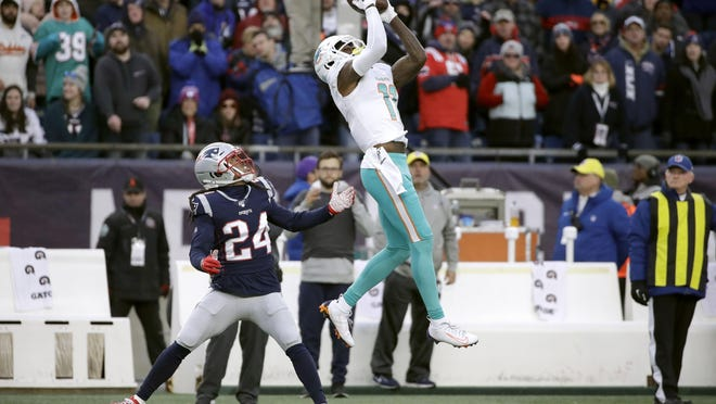 Dolphins receiver DeVante Parker catches a pass over New England Patriots cornerback Stephon Gilmore in the 2019 finale.