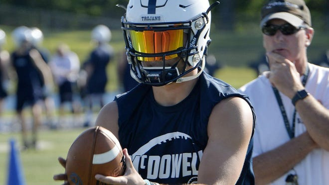 McDowell quarterback Chris Juchno runs a play during a workout on July 14, 2020, at Gus Anderson Field in Millcreek Township.