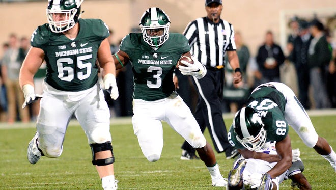 Michigan State University sophomore running back LJ Scott (3) finds an avenue to run for yardage against Furman in the Spartan's 28-13 opening game victory Friday, Sept. 2, 2016, in East Lansing. Scott finished with 108 yards on 20 carries and a touchdown.