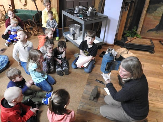 Children look at a metal lantern held by Patti Malenke, director of the Johnson-Humrickhouse Museum, during a program about using wood, glass, metal and clay as creative materials.