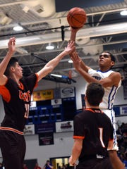 Zanesville's Aronde Myers goes up for a shot against two Meadowbrook defenders in Tuesday's 59-51 loss.