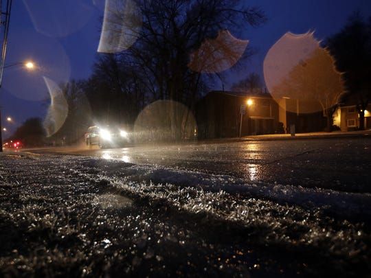 The headlights from a vehicle traveling down Calumet Avenue illuminate a stretch of frozen grass Tuesday, Feb. 20, 2018, in Appleton, Wis.